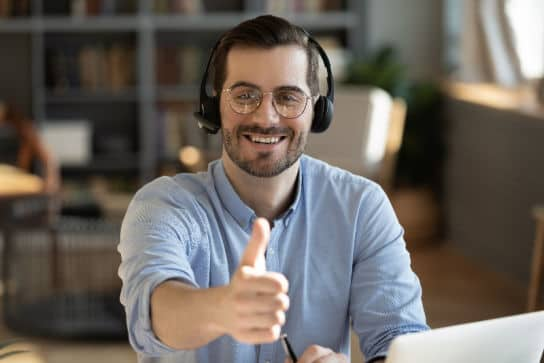 Man wearing headset giving thumbs up